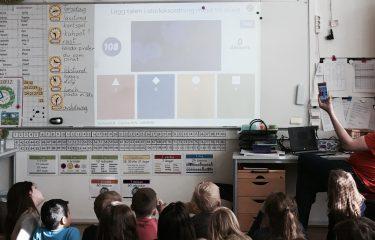 Barn sitter på golvet framför tavla där presentation projiceras.