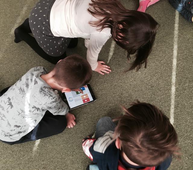 Tre barn sitter på golvet och jobbar med ipad.