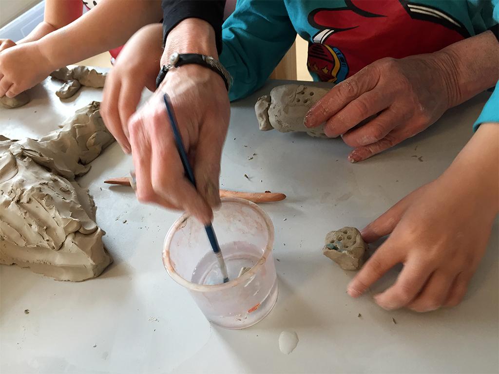 Barnhänder gör figur i lera.