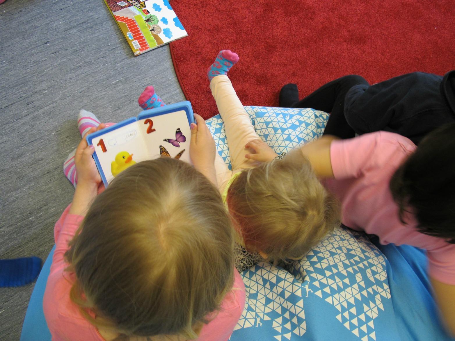 Barn sitter i pedagogs knä och läser bok.