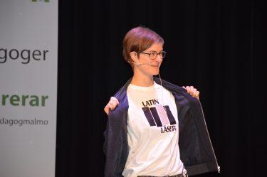 Kvinna på scen visar upp t-shirt.