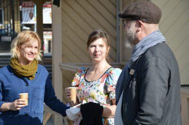 Två kvinnor och en man dricker kaffe och samtalar utomhus.