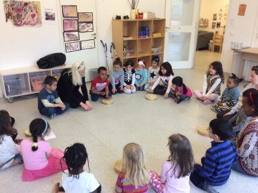 Barn sitter i cirkel och trummar.