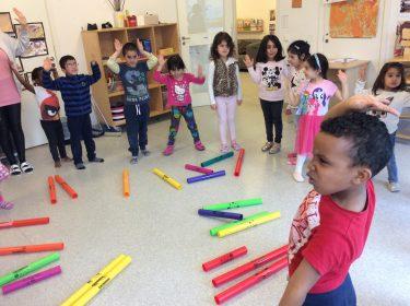 Barn står i cirkel och dansar.