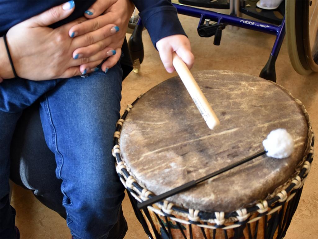 Händer slår på trumma med pinne.