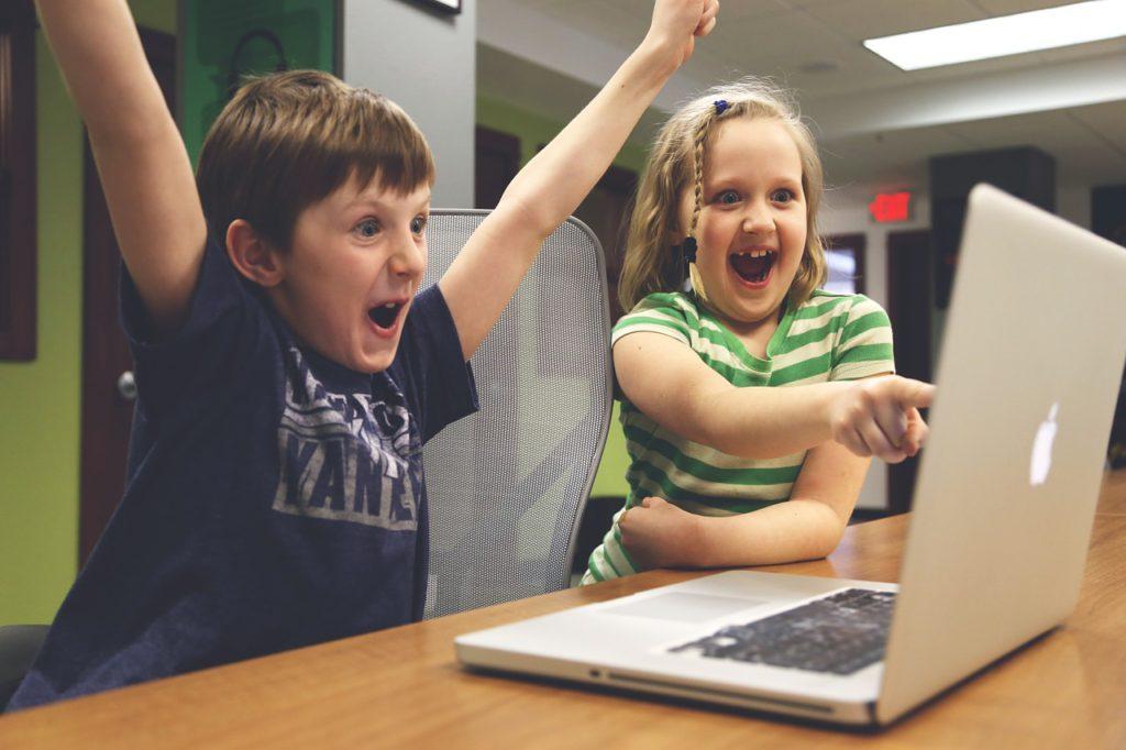 Två barn pekar på datorn och sträcker händerna i luften i segergest.