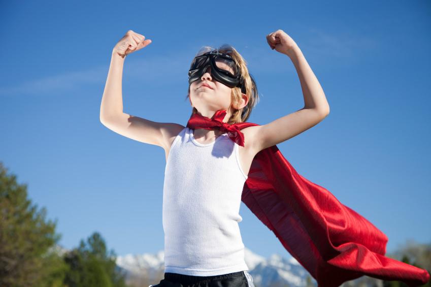 Pojke med röd mantel visar armmuskler.