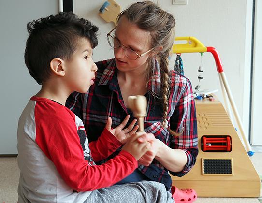 Barn och pedagog provar att spela på träinstrument.