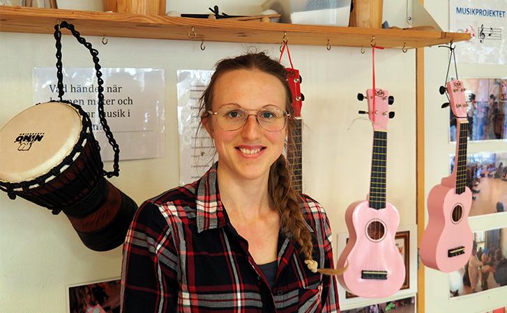 Kvinna sitter framför upphängda trummor och ukuleles.