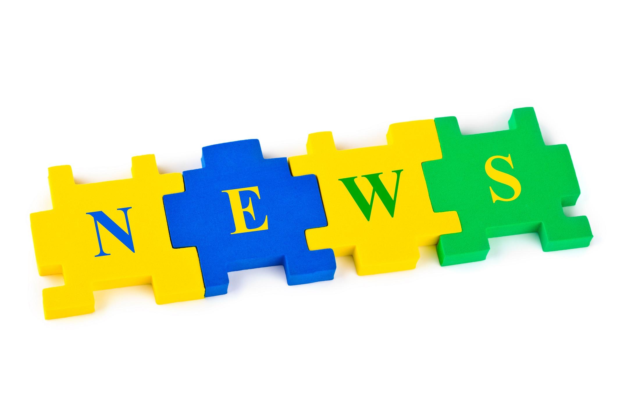 Ordet news bildas av färgglada pusselbitar.