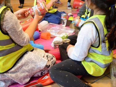 Barn sitter på golvet med pysselmaterial framför sig.