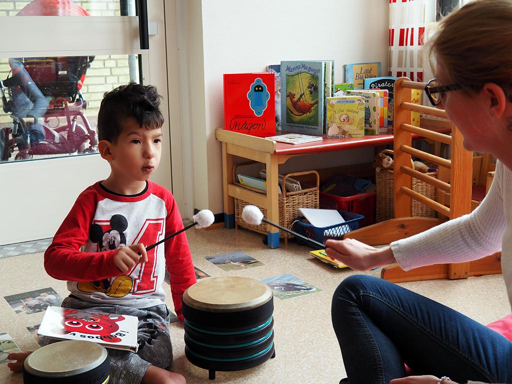 Barn och pedagog trummar med pinne.