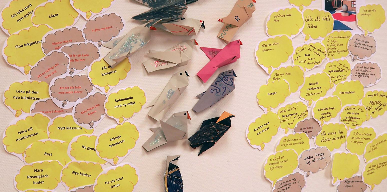 Fåglar av papp och pratbubblor sitter på vägg.