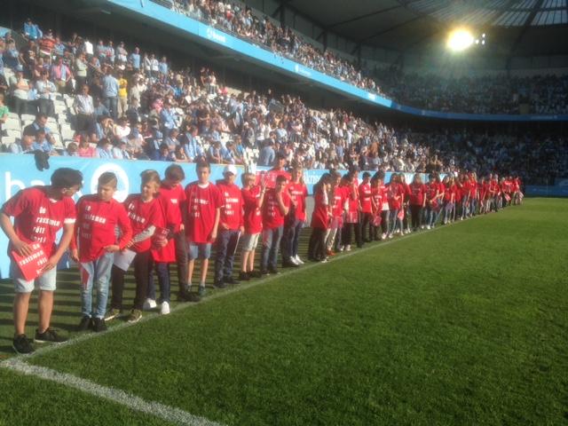 Elever i röda t-shirtar står vid linjen av fotbollsplan.