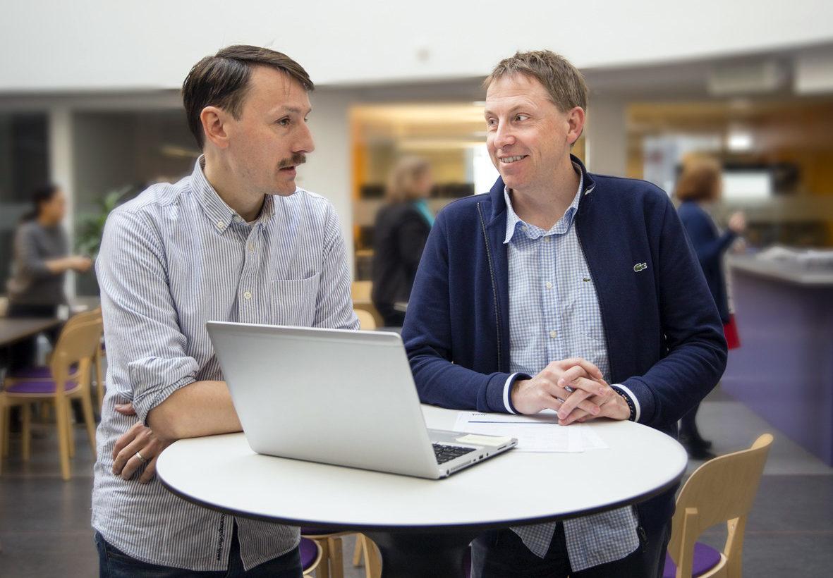 Två män står vid ståbord där en dator står uppfälld.