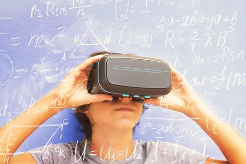 Barn håller upp VR-glasögon framför sitt ansikte.