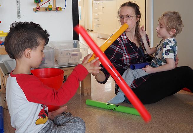 Barn och pedagog provar att blåsa i stora rör.