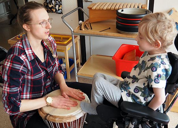 Barn sitter i rullstol med fötter på trumma som pedagog håller i.
