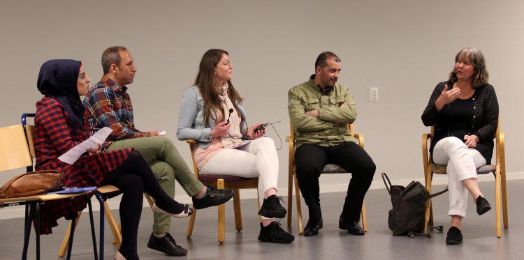 Fem personer sitter på scen i panelsamtal.