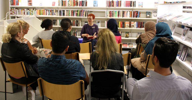 Kvinna läser ur en bok för publik.