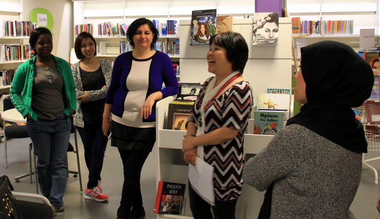 Fem kvinnor står i bibliotek.