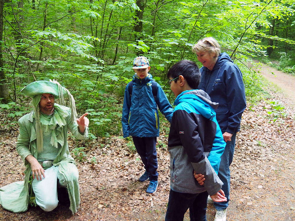 Två barn och pedagog träffar utklädd man i skogen.