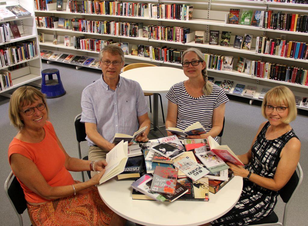Fyra personer sitter runt bord som är fyllt med olika böcker.