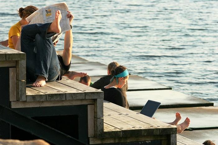 Kvinnor vid bänk på havet.