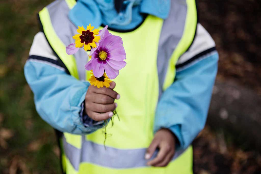 Barn håller upp bukett med blommor.