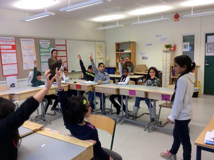 Elev står längst fram i klassrum och visar charad för klasskompisarna.