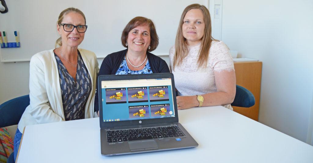 Tre pedagoger sitter bakom en uppfälld laptop.