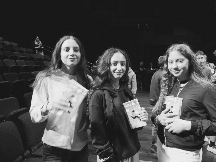 Tre elever håller upp sina egna böcker.