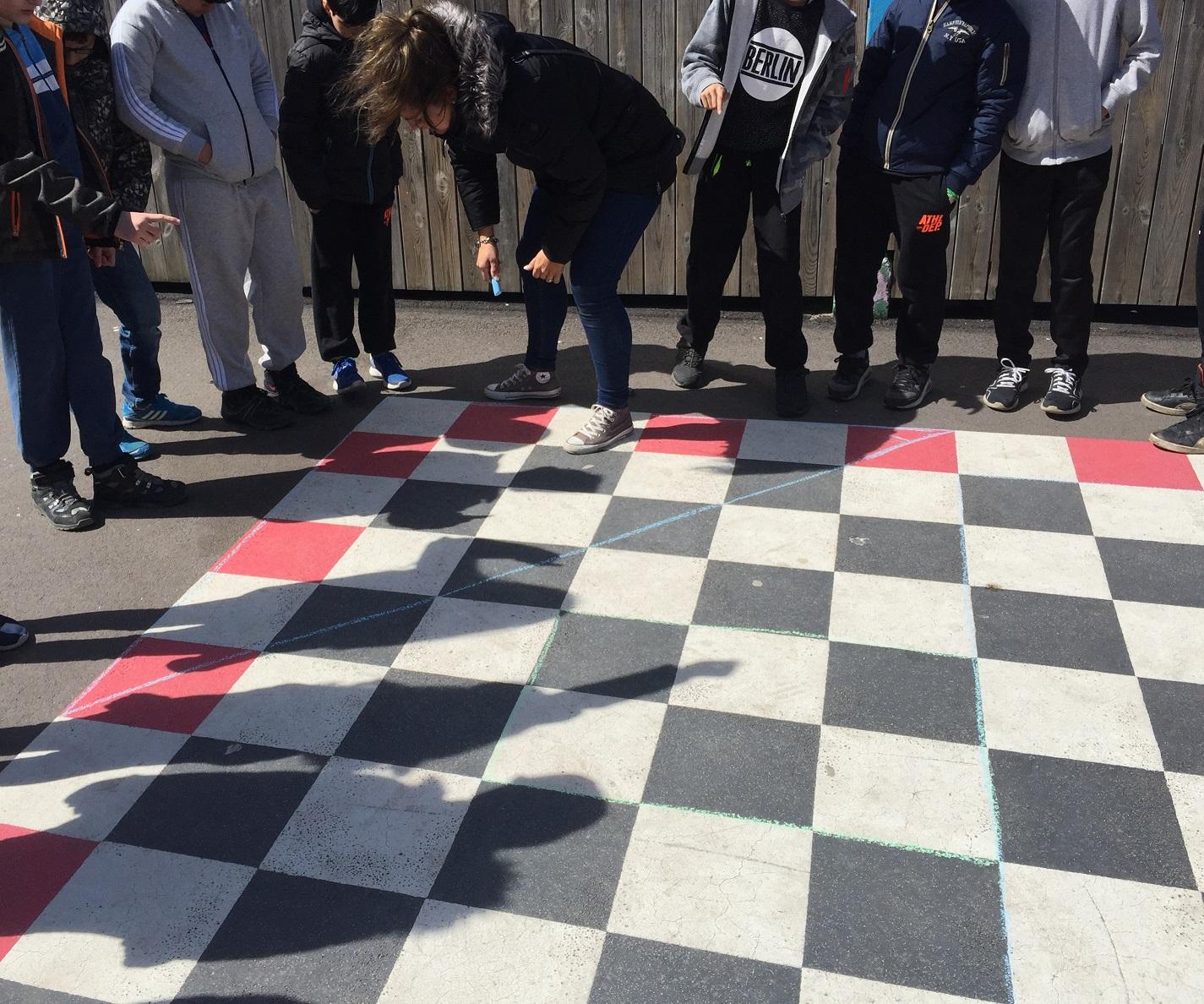 Barn står vid rutor som bildar kvadrat.