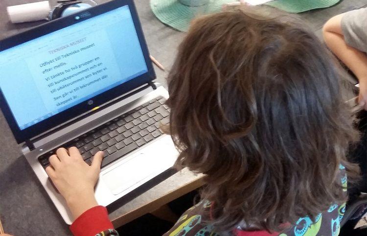 Barn skriver på dator.