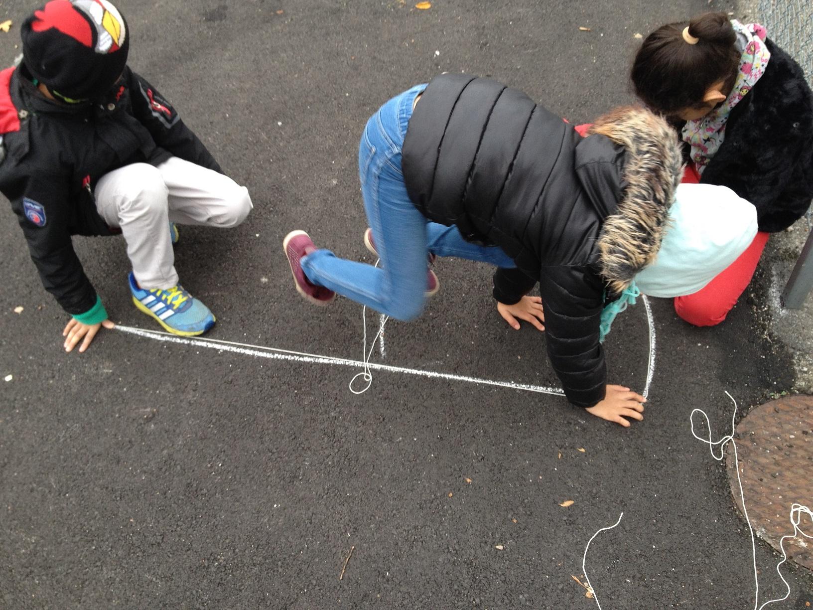 Elever mäter på skolgård.