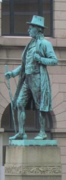 Staty av man med hög hatt.