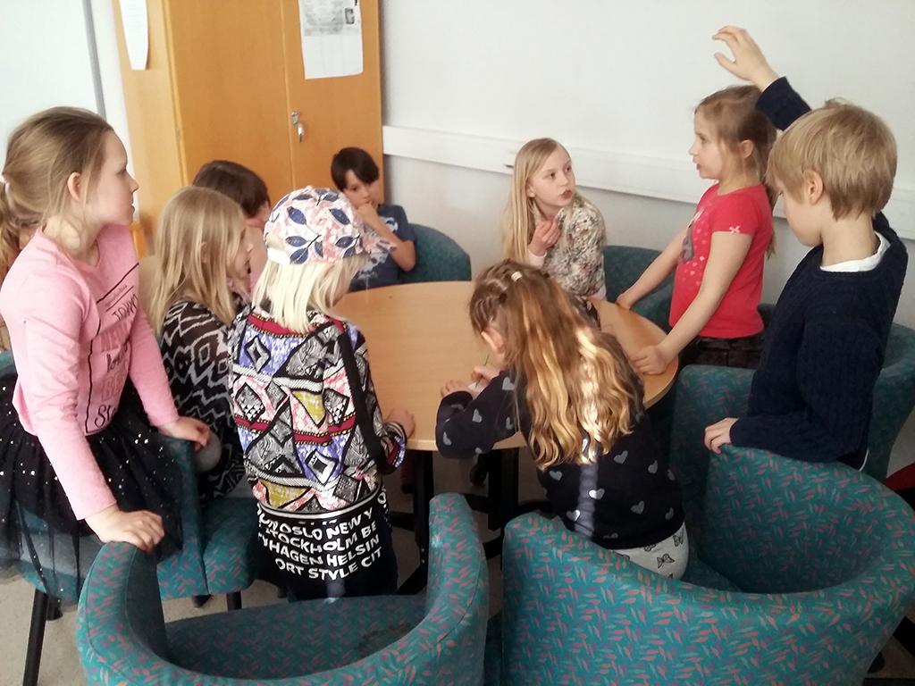 Barn runt ett bord pratar och samarbetar.