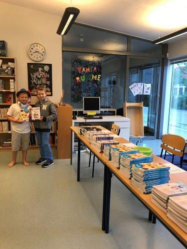 Elever håller upp böcker.