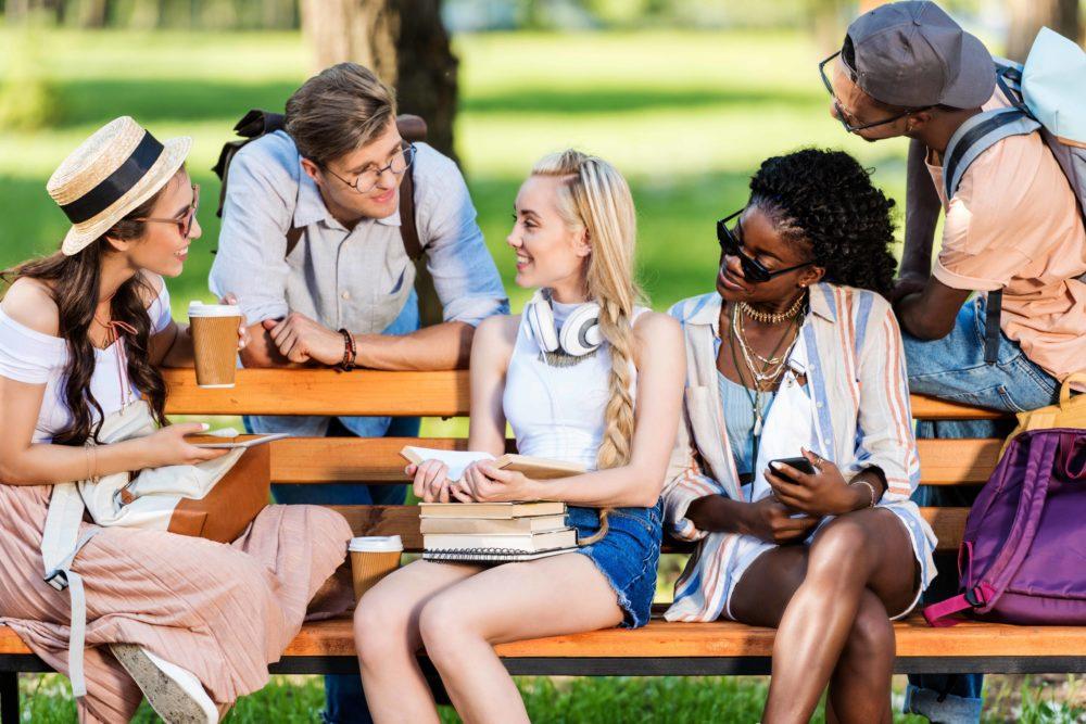 Ungdomar sitte rpå bänk och pratar.