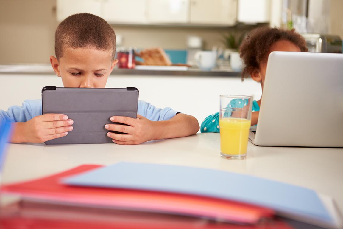 Två barn jobbar med laptop och ipad.