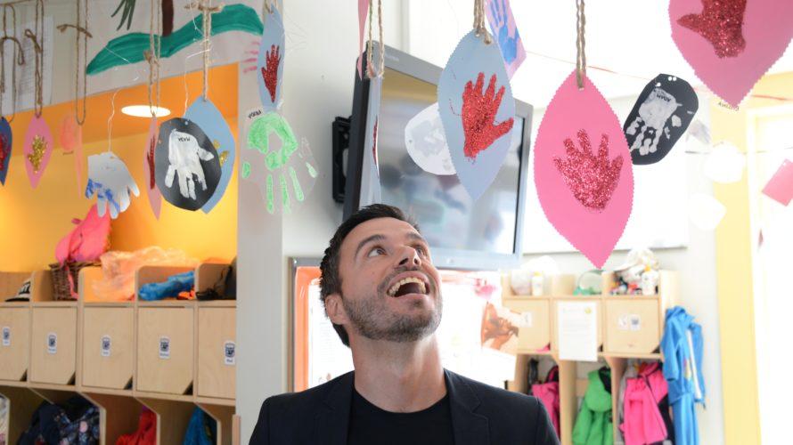 Gezim Isufi tittar upp på barnens konstverk som hänger i taket.