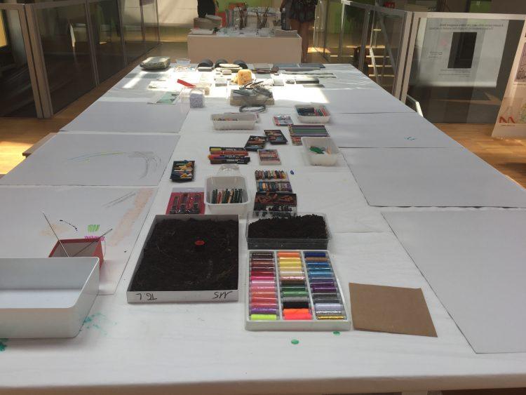 Papper och pennor, färger och kritor står uppdukat på bänk.