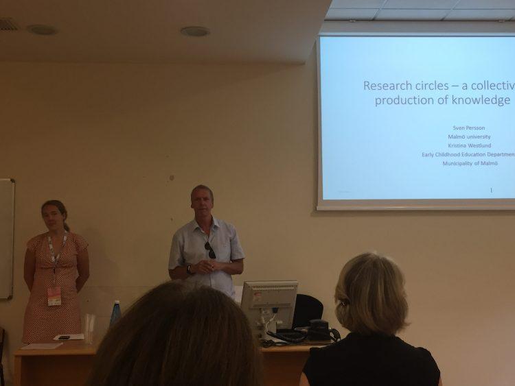 Man och kvinna föreläser framför projicerad presentation.
