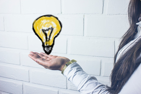 Hand håller upp tecknad tänd glödlampa.