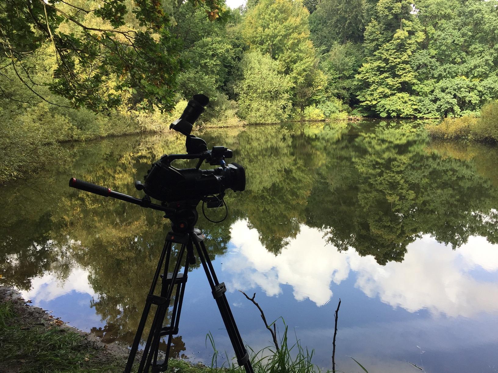 Filmkamera står uppställd vid damm.