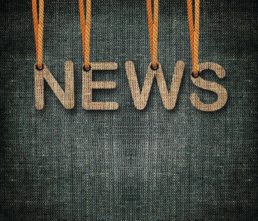 Ordet news hänger i trådar på en mörk bakgrund.