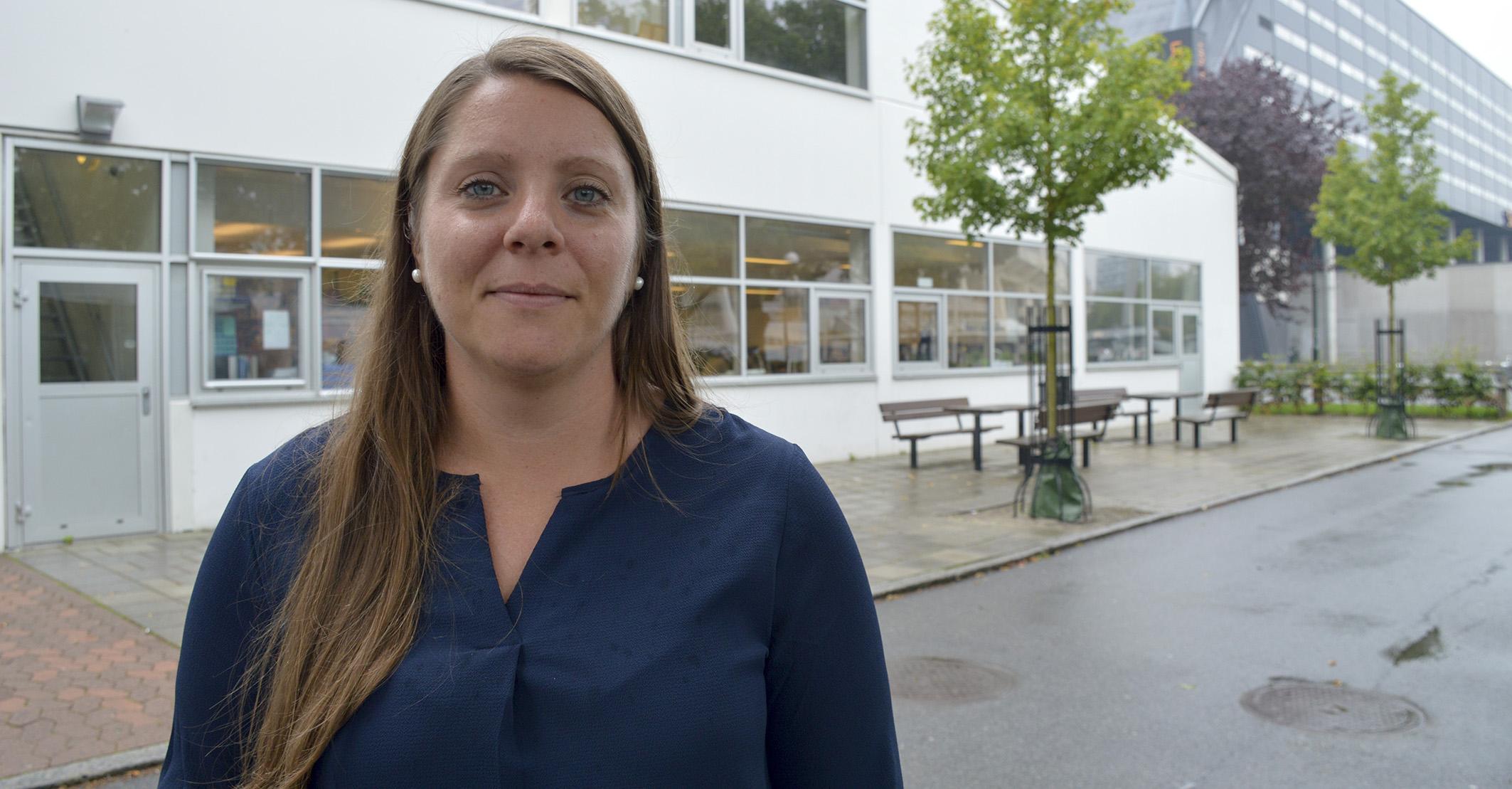 Kvinna framför skolbyggnad.