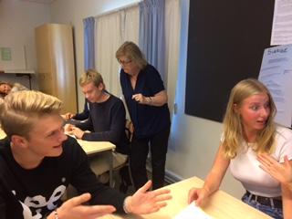 Elever diskuterar i klassrum och läraren går runt.