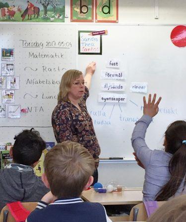 Kvinna undervisar vid tavla.
