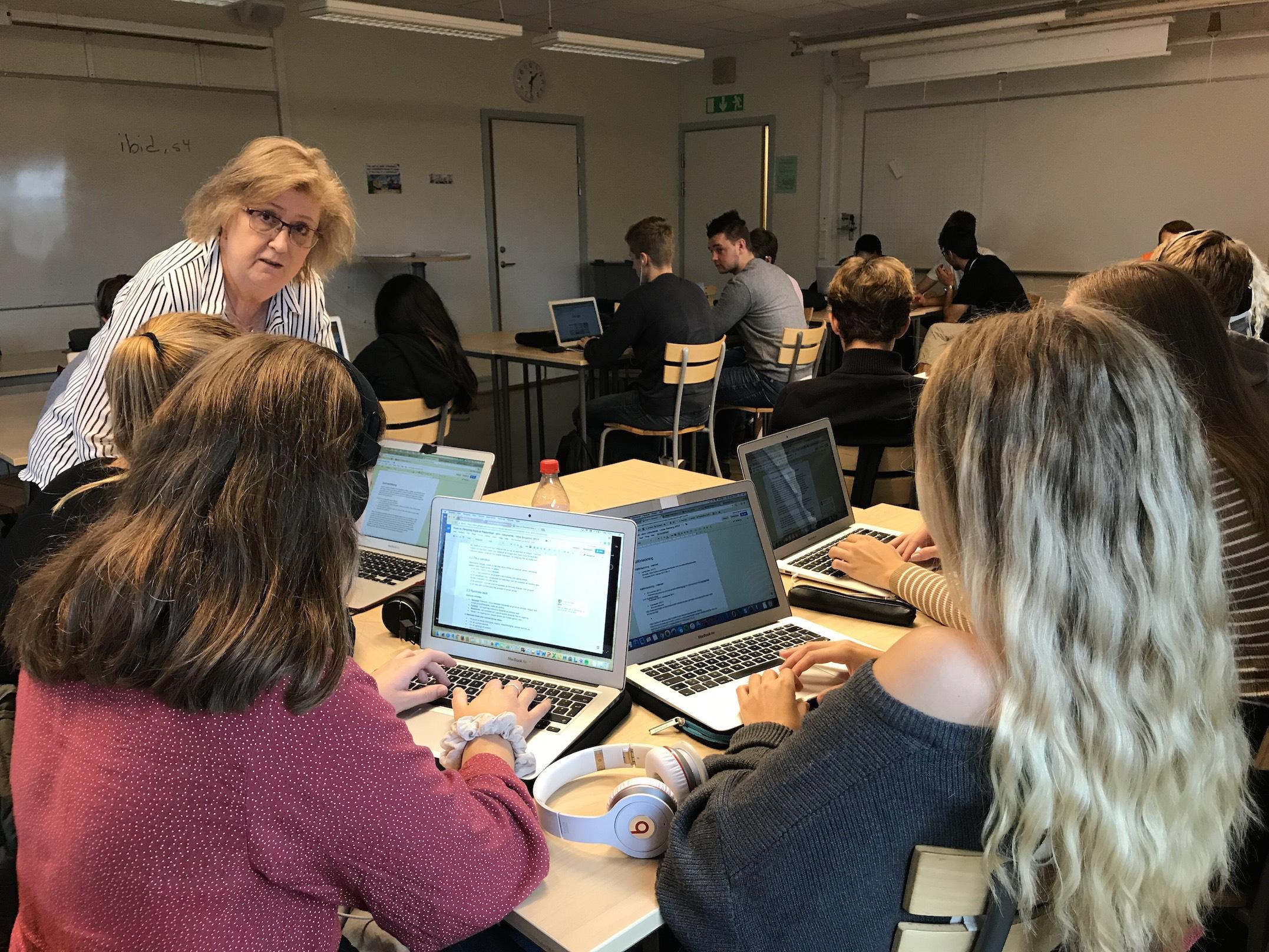 Eva Henriksson Garatea lutar sig över bord där elever jobbar med sina datorer.